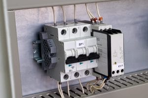 Modular circuit breaker and phase change control relay on the circuit Board in the electrical Cabinet. The devices are connected to the mains by electrical wires. Convenient and modern technology.
