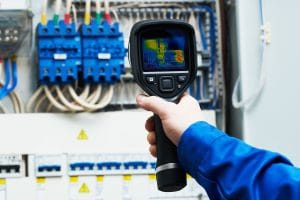 electrician use thermal imaging camera for overheating temperature inspection of electrical equipment