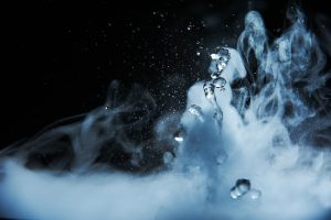 Boiling water splash with steam on black background closeup.