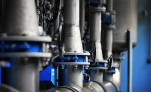 Large industrial water treatment and boiler room. Piping, flanges, butterlfy valves, rusty and corroded bolts