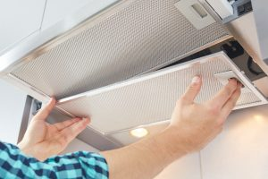 Mans hands removing a filter from cooker hood for cleaning or service. Replacing filter in kitchen hood. Modern kitchen fan.